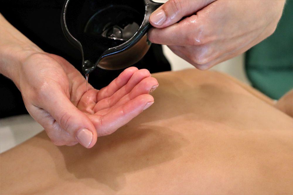 Nalewanie olejku do masażu na dłoń